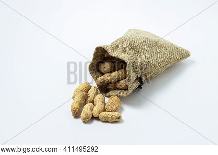 Peanuts On A White Background. Peanuts In A Small Bag. Peanuts In Shell