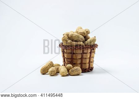 Peanuts On A White Background. Peanuts In A Small Basket. Peanuts In Shell