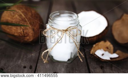Broken Coconuts On Gray Wooden Background With Jar Of Raw Organic Extra Virgin Coconut Oil And Palm