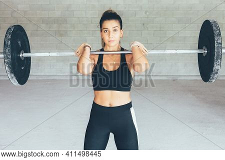 Close Up Of A Fitness Young Woman With A Barbell Over The Shoulders Does A Exercises Routine In The