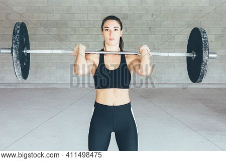 Close Up Of A Fitness Young Woman With A Barbell Over The Shoulders Doing A Exercises Routine In The