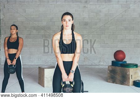 Pair Of Young Fit Women Doing Kettlebell Exercises At The Gym. Fitness Exercises Material At The Bac