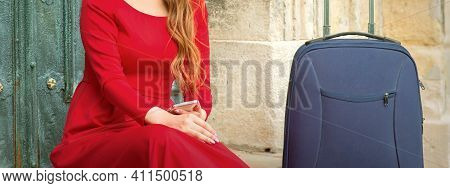 Portrait Of A Beautiful Young Caucasian Traveling Woman Sitting At The Door With Suitcase Smiling An