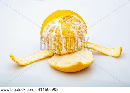 Half Peeled Clementine Against A White Background