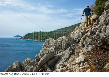 Hiking Lycian way. Man is trekking on steep tricky rocky path along Mediterranean sea coast on Lycian Way trail near Kalkan, Trekking in Turkey, outdoor activity