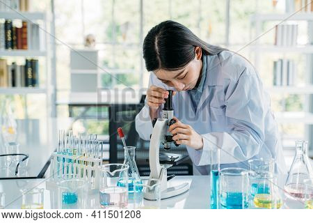 Young Woman Asian Scientist Wearing Medical Labcoat Performing Research In Lab While Seeing Elements