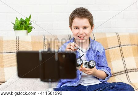 Child Is Blogging About Robotics At Home, Boy Records A Video Blog On Camera, Holds Parts Of Constru