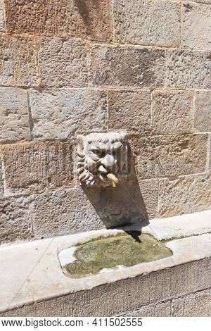 Gothic Stone Head Of Public Fontain Of The Church In Solsona, Lleida, Catalonia, Spain.