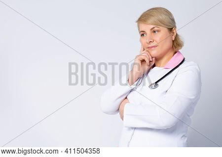 Thoughtful Senior Female Doctor Looking In Distance Lost In Thoughts. Worried Old Physician Thinking