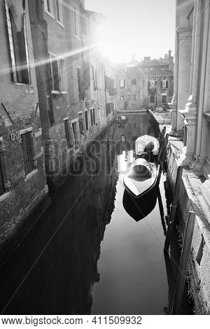Perspective of a venetian canal moored motorboats on summer sunnu day, Venice, Italy. Black and white photography, cityscape