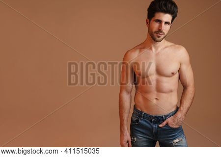 Shirtless masculine man posing and looking at camera isolated over beige background