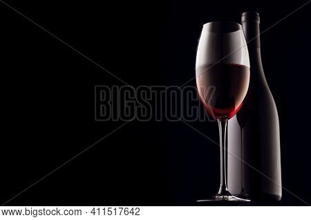 Red Wine, Glass And Bottle On A Black Background, Close-up Of Copy Space