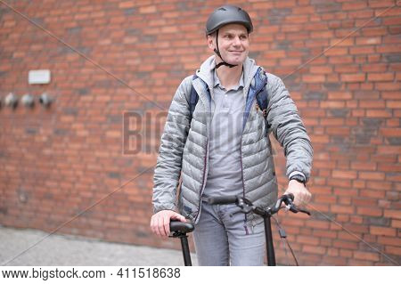 Mature Caucasian man in a bicycle helmet on his bike in a city against red brick wall