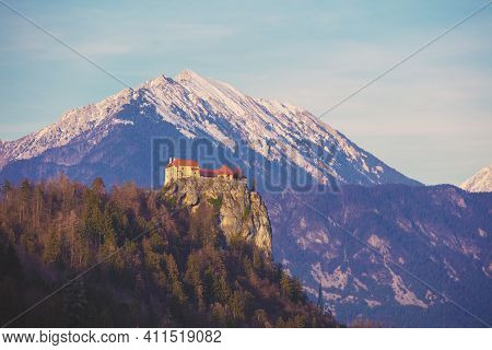 View Of Bled Castle Against Snowy Mountains From Bled Lake