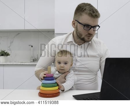 Handsome Bearded Blond Man Wearing White Shirt Working In The Kithen, At Home With Laptop, Holding C