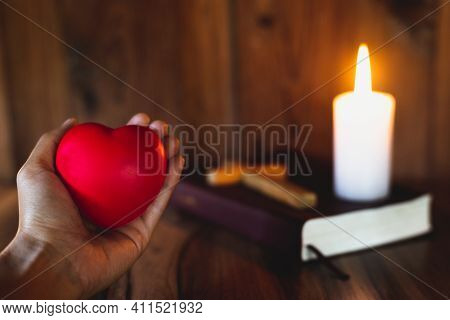 The Heart Symbol On A Woman's Hand A Candle Lit Up The Scriptures. Pray For God's Blessing With Fait