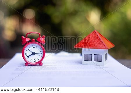 The Orange Roof House Is Placed Close To The Red Alarm Clock. Real Estate Timing Ideas, Mortgages, H