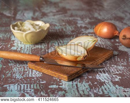 Onions Cut Into Halves On A Kitchen Board And A Knife, Whole Onions Chopped Onions