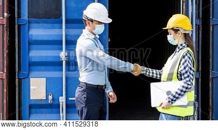 Businessman And Engineer Woman Shake Hands As Hello In The Container Cargo Harbor To Loading Contain