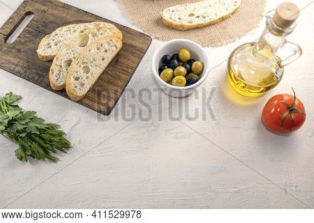 Sliced Bread On Serving Board Served With Olives, Tomatoes, Olive Oil And Fresh Herbs On White Table