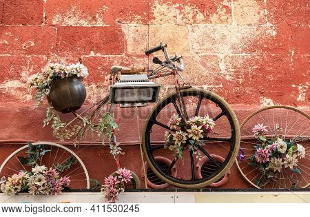 An Old Bicycle As A Flowerbed Hanging On The Wall Of A Building In Gravina In Puglia . Italy