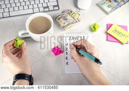 Female Hands Written Word Invest In Notepad, Cup, Keyboard, Stickers, Pen And Money On Table. Concep