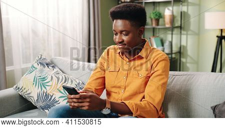 Close Up Of Handsome Young African American Joyful Guy Sitting On Couch In Apartment In Cozy Room Al