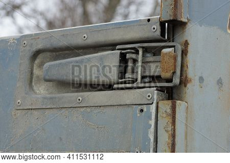 Part Of An Iron Dirty Side Of A Truck With A Large Latch In Rust