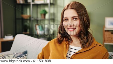 Close Up Of Beautiful Caucasian Happy Cheerful Young Female Sitting In Room On Sofa In Apartment Res