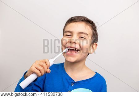 Six Years Old Boy With Electric Toothbrush On White Background. Close Up. Dental Care.