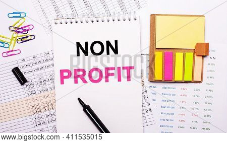 A Notebook With The Words Non Profit, A Marker, Colored Paper Clips And Bright Note Paper Lie On The