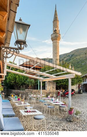 Outdoor cafe and minaret of the mosque in old town of Mostar, Bosnia and Herzegovina