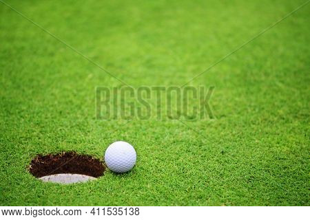 Golf Ball Close To Hole, On Lip Of Cup On Green Of Golf Course Background With Copy Space For Text B