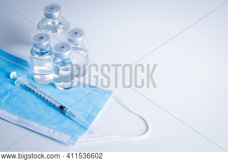 Anti-virus Vaccine Bottle With Syringe And Mask Placed On A White Background Concept Of Vaccine For