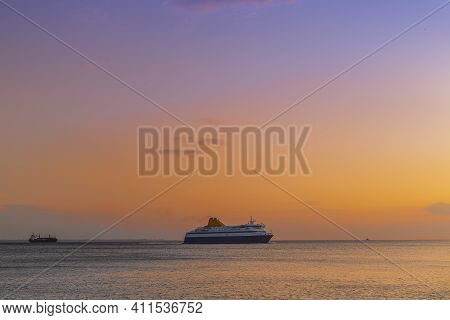 Passenger Ship Sailing To City Seaport At Sunset In Thessaloniki, Greece. Evening View Of Commercial