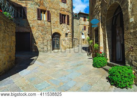 Beautiful Tuscan Street View. Rustic Stone Houses And Paved Street. Decorated Entrances With Ornamen