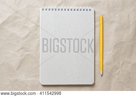 Gray Notepad With White Coiled Spring And Pencil On A Background Of Beige Crumpled Craft Paper. With