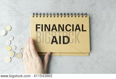 Financial Aid Text Written On A Notebook With Hand