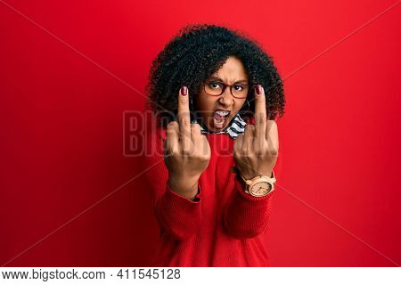 Beautiful african american woman with afro hair wearing sweater and glasses showing middle finger doing fuck you bad expression, provocation and rude attitude. screaming excited