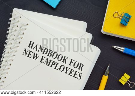Stack Of Handbook For New Employees On The Desk.