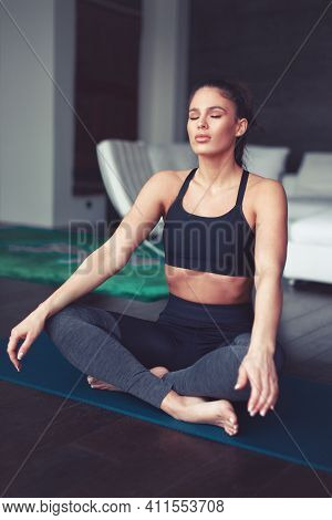Young Caucasian Woman Meditating During Yoga Exercise Indoors, Eyes Closed