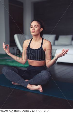 Young Caucasian Woman Meditating During Yoga Exercise Indoors, Eyes Closed, Mental Health