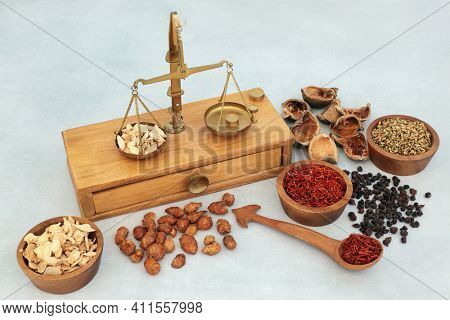 Chinese herbs and spice used in traditional herbal medicine with old apothecary brass weighing scales. Alternative health care concept.