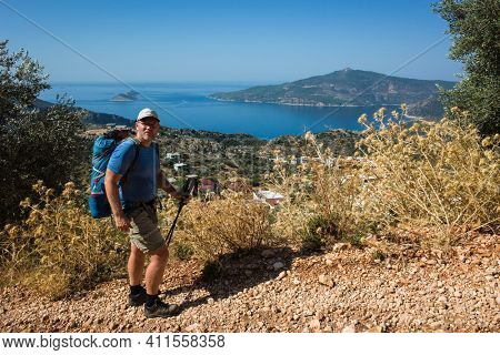 Hiking Lycian way. Man tourist is standing on path over Mediterranean sea coast on Lycian Way trail above Kalkan, Trekking in Turkey, outdoor activity