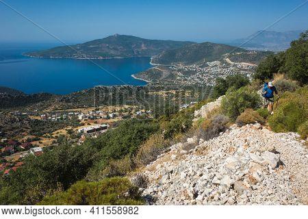 Hiking Lycian way. Man is trekking on stony path high above Mediterranean sea coast on Lycian Way trail near Kalkan, Trekking in Turkey, outdoor activity