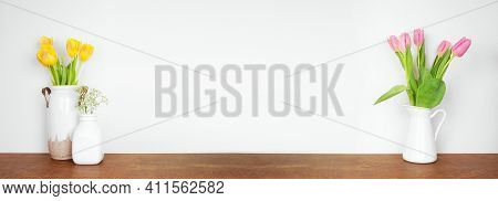 Home Decor On A Shelf. Vases Of Spring Flowers On A Wood Shelf Against A White Wall. Banner With Cop