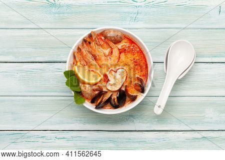 Traditional Thai soup Tom Yum kung with seafood, coconut milk and chili pepper. Top view flat lay