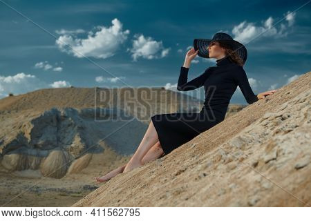 Full length portrait of stunning fashionable lady is posing in elegant black dress and wide-brimmed hat in the desert. Vacation in hot countries.
