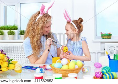 Easter holiday. Happy mother with her daughter with bunny ears are painting easter eggs for Easter.  Loving family concept.