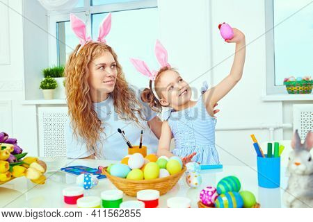 Loving family concept. Happy mother with her daughter with bunny ears are preparing for Easter. Easter holiday.